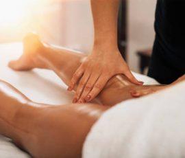 Anti cellulite massage. Masseuse massaging a calf area of a female leg to reduce cellulite